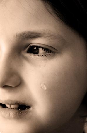 若い女の子の顔の頬を降ろすの涙を泣いています。