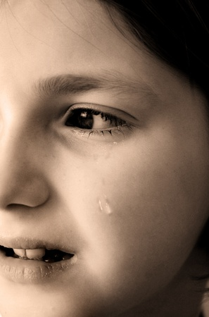 Young girl crying with tear rolling down cheek of face photo