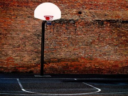 basketball hoop: Urban basketball court in neighborhood with old buildings