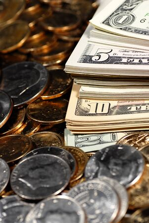 heap: Coins and dollar bills representing wealth and savings Stock Photo