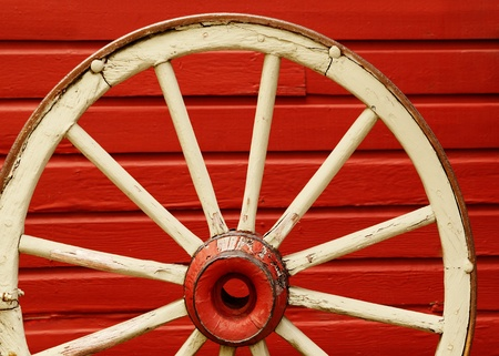 spoke: Old weathered wagon wheel leaning against red wall  Stock Photo
