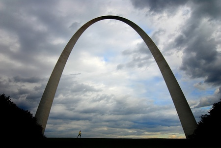 st  louis arch: Runner running under the St. Louis Arch with Clouds in the Sky