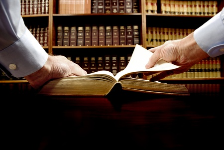 law: Hands holding an old book with library in background Stock Photo