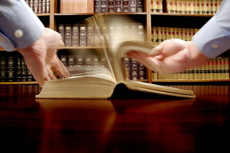Hands turning pages in old law book with library in background photo