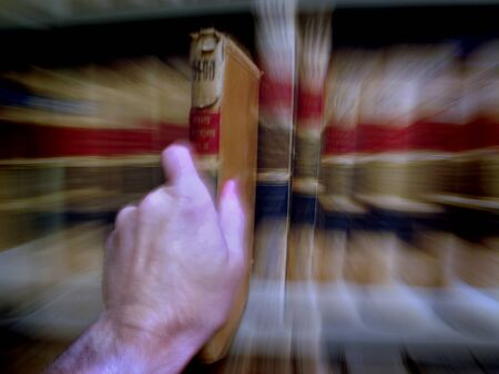 Close up of hand pulling out a book on shelf photo