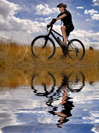 Young Woman Riding Mountain Bike in Wilderness Reflected in Water photo