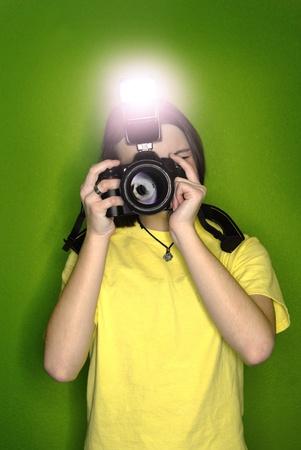photo studio: Girl photographer taking photo with digital camera and flash Stock Photo