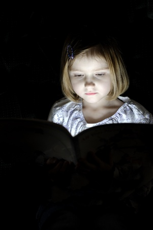 secretly: Little girl reading book in dark with light shining on face Stock Photo