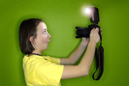 Girl photographer taking photo of self with digital camera and flash