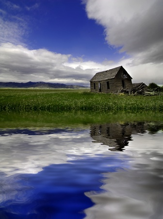 Old cabin and field with clouds in sky reflected in water of lake