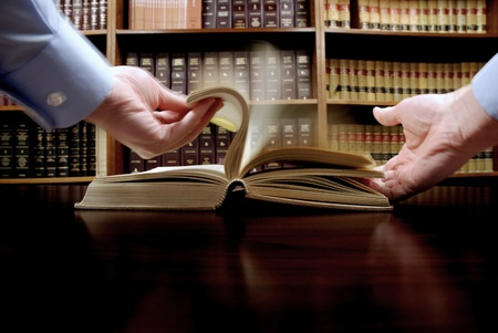 statute: Hands holding an old book with library in background Stock Photo