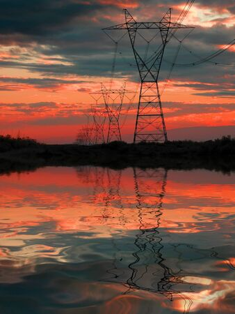 modernize: Powerlines with sunset in sky and reflection in water Stock Photo