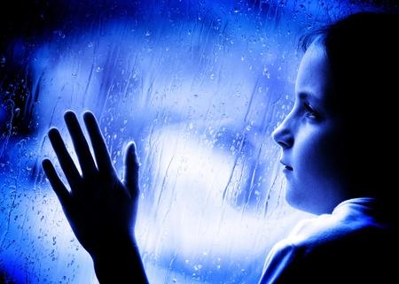 desilusion: Ni�a mirando por la ventana en un d�a lluvioso Foto de archivo