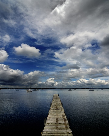 Dock on lake or sea of water with dramatic sky photo