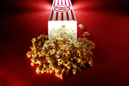 Popcorn for a movie in a popcorn holder and spilling out Stock Photo - 12711070