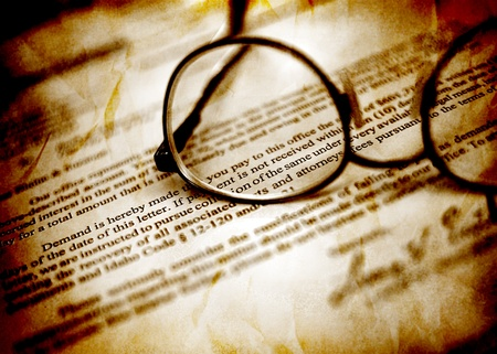 Closeup of Eyeglasses on top of business document with signature
