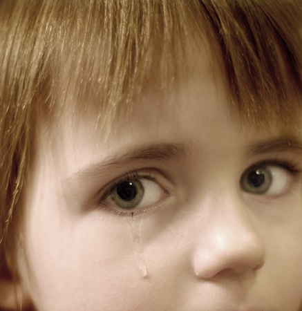 crying child: Portrait of little girl crying with tears rolling down her cheeks