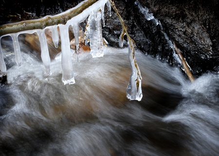 droop: Stream in winter with icicles hanging from tree branches Stock Photo