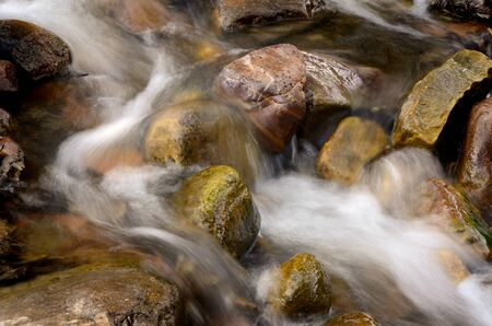 rushing water: Creek or stream water flowing past rocks and stones