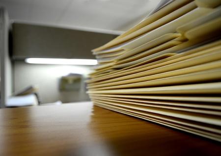 legal document: Mesa o estantería llena de carpetas y archivos en una oficina
