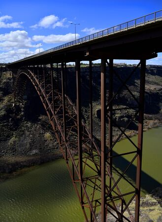 transportaion: Long metal bridge for vehicle transportaion spaning caynon above river Stock Photo