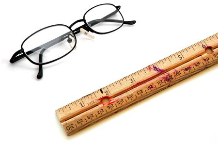 Detailed closeup of old marked up ruler adn glasses for education photo