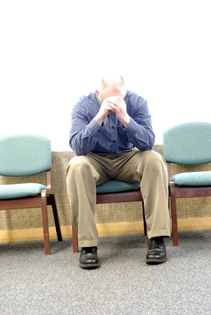 Man grieving with sorrow and sadness in waiting room