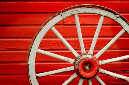 Old weathered roue de chariot appuyé contre mur peint en rouge