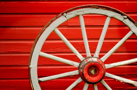 Old weathered wagon wheel leaning against painted red wall  photo