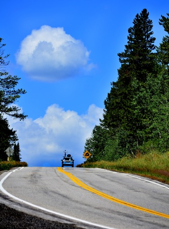 Car with bike on top driving on mountain road photo