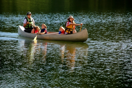 canoe paddle: Family in a canoe on a lake in the summer