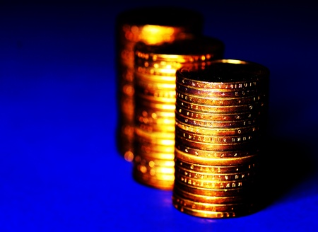 Several stacks of gold coins on blue background photo