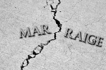 Symbool van gebroken huwelijk met barst in beton en woord Stockfoto