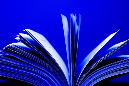 A large single book sitting with pages open on a desk and blue background
