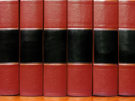 Row of old red leather books on a shelf with blank covers photo