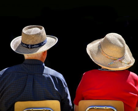 married couples: Old couple sitting in chairs wearing straw hats with black background