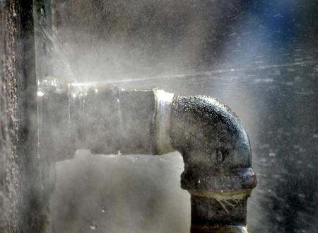 lekken: Oude roestige pijp met lek en het water spuit uit