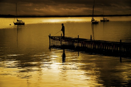 Dock floating in lake with sky and fisherman photo