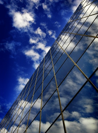 refelction: Office building details reflecting blue sky and clouds in windows
