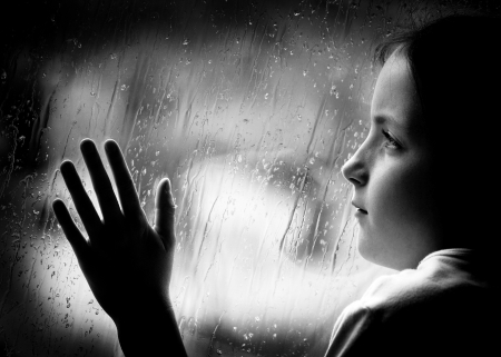 Girl looking out window on a rainy day photo