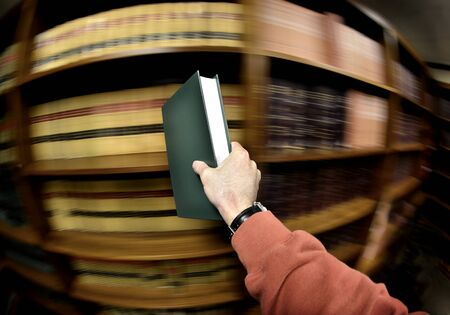 Hand holding book in an old library in background photo