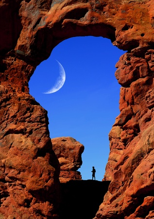 Silhouette of Man hiking under an Arch in Arches National Park photo