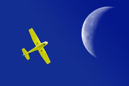 Yellow airplane flying across deep blue sky with large moon photo
