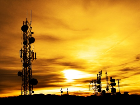 antenna: Several radio towers with sunset sky in background