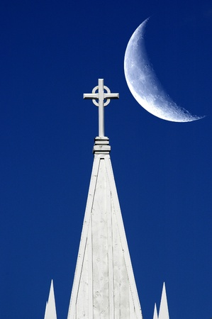 Church steeple and cross with blue sky and large crescent moon photo