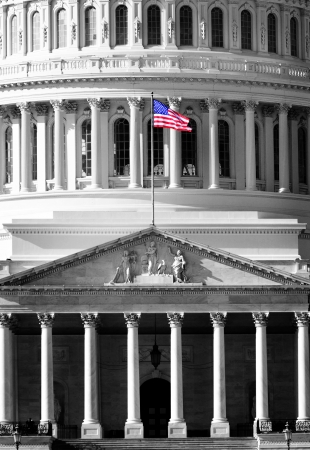 United State Capitol Building for congress with american flag flowing in breeze and columns in background Stock Photo