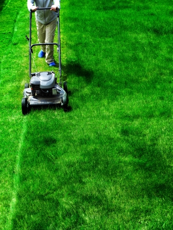 lawn mower: Young Girl Mowing green grass lawn with push mower