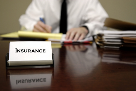 health insurance: Man sitting at desk with files and insurance business card