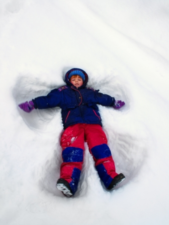 children at play: Child playing in the winter making a snow angel Stock Photo