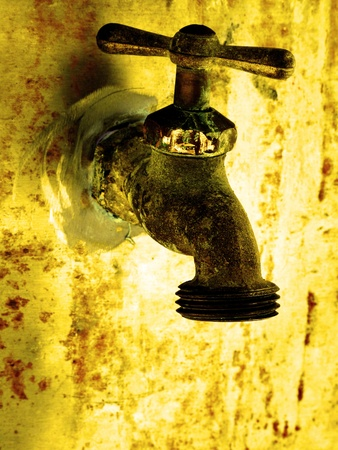 Water faucet dripping water with golden background on hot day Imagens